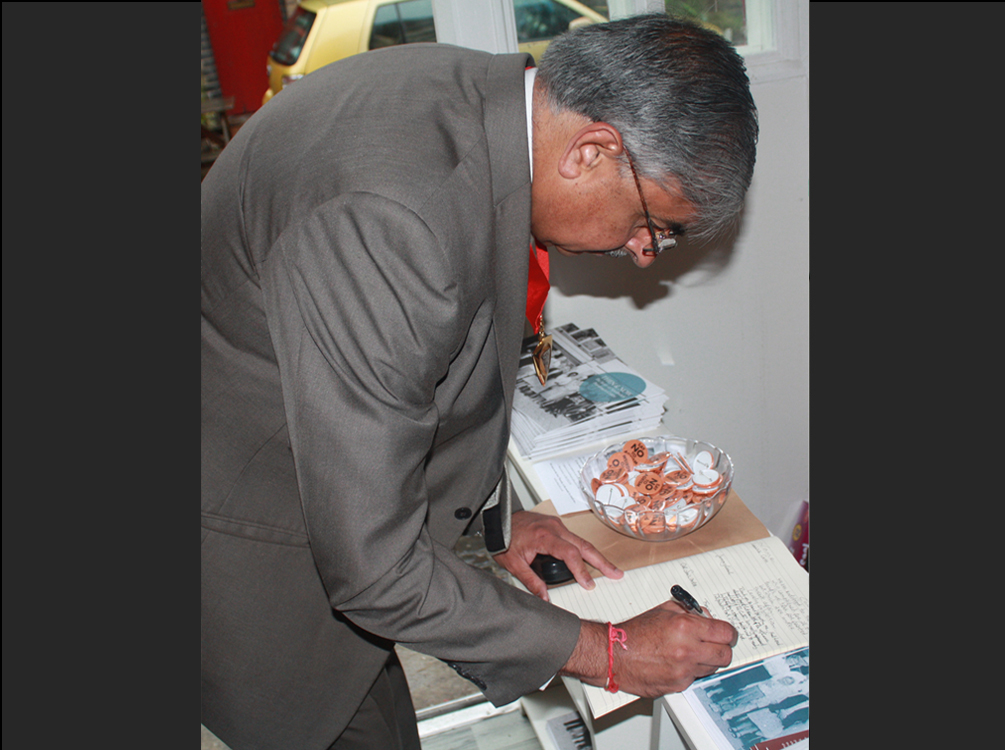 Signing the guestbook book at Then and Now event